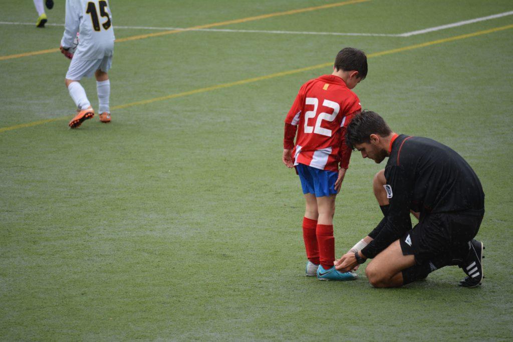 サッカーの審判が選手に足のチェックをしている