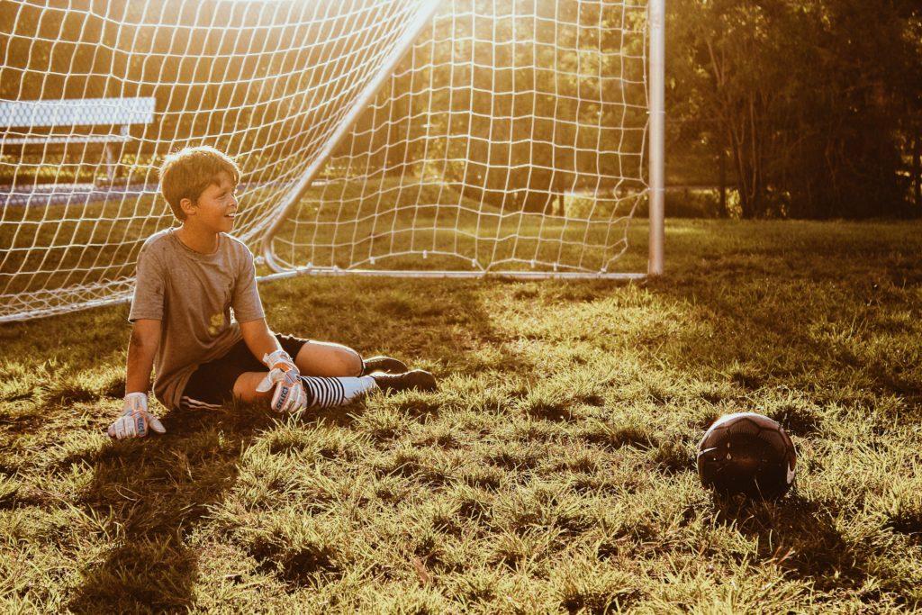 少年がゴールキーパーの前で座っているところ